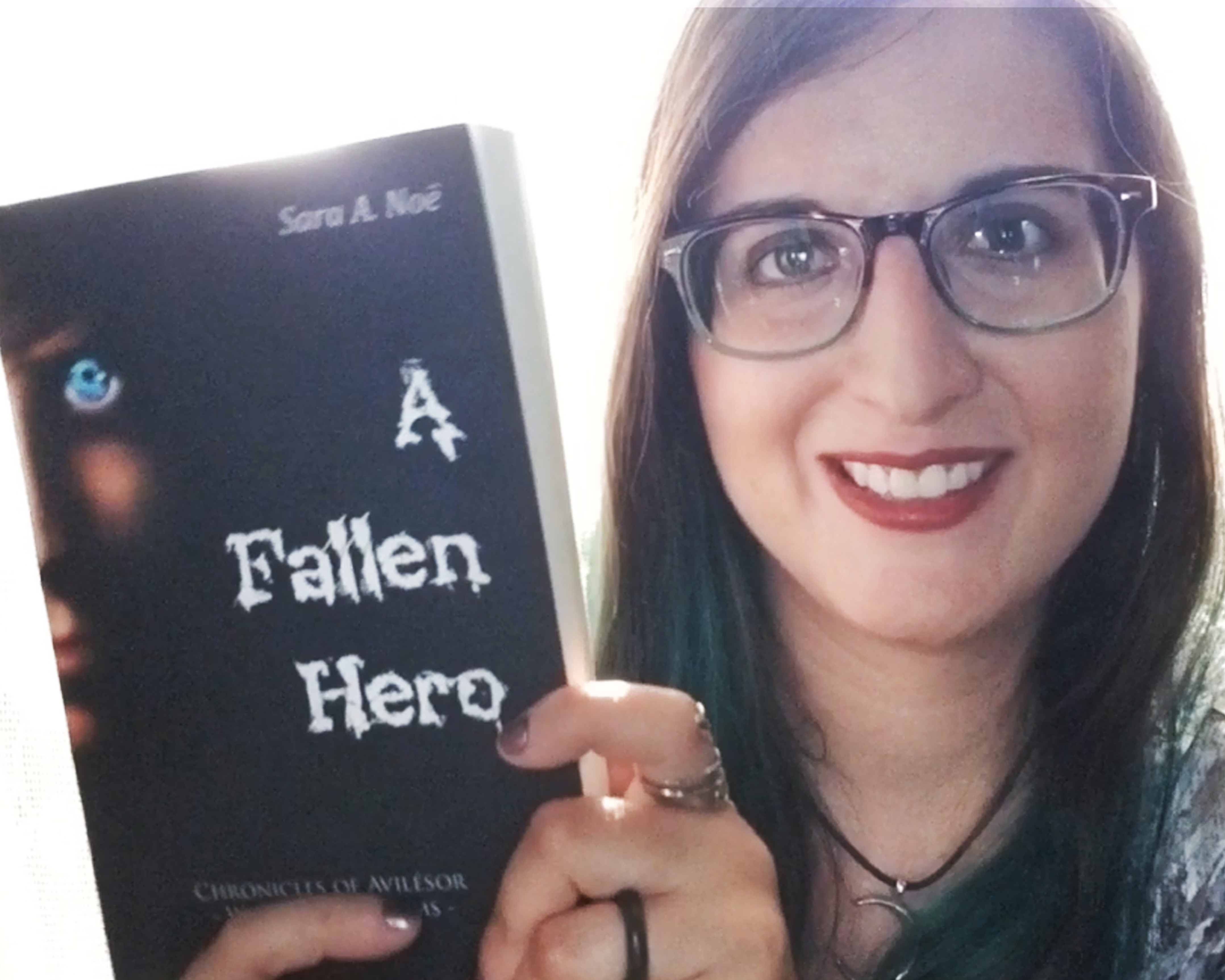 Author Sara A. Noë holding her first novel Chronicles of Avilésor: War of the Realm, A Fallen Hero