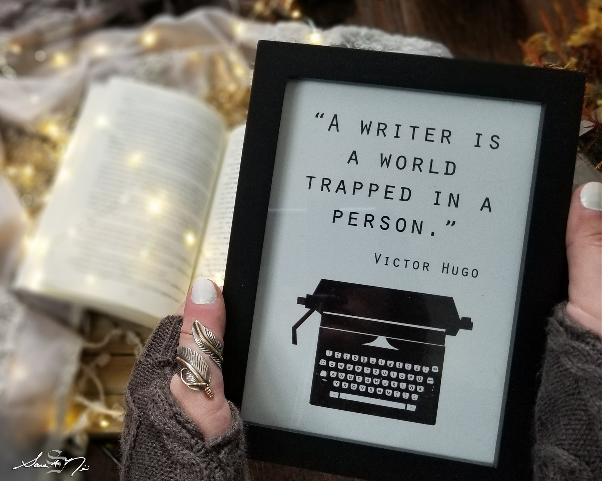 Writing quote Victor Hugo with book and lights in the background